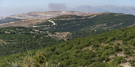 panorama of the Israel Lebanon border in the upper galillee and golan heights with mt hermon and a hazy smokey sky in the background Stock Photo