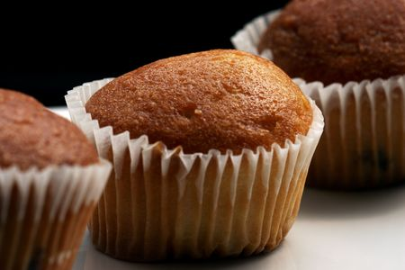 doughy: Sweet threesome muffin on black background Stock Photo