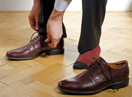 putting: man putting on shoes Stock Photo