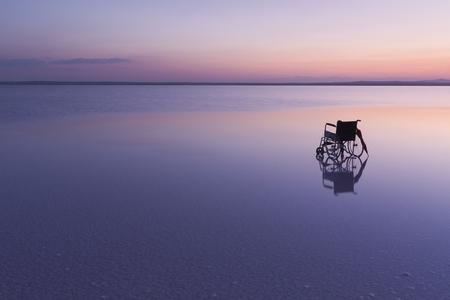 湖で美しい色と夕焼けの空の車椅子