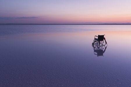 Empty wheelchair on the lake at sunset with beautiful colours
