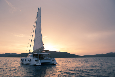 Yacht - Catamaran in the ocean. Sailing at sunset Standard-Bild
