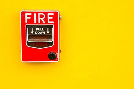 glasses: Fire alarm switch on yellow wall Stock Photo