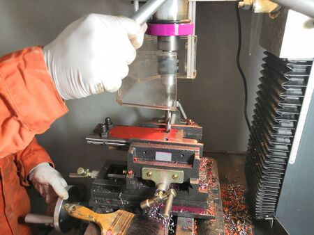 The man is drilling steel with a drilling machine. Drill bit is drilling steel sheets. There is a hole on the steel plate caused by the punching force of the machine.