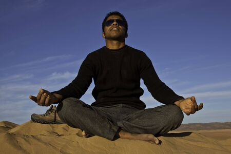 attractive young african man meditating in the desert photo