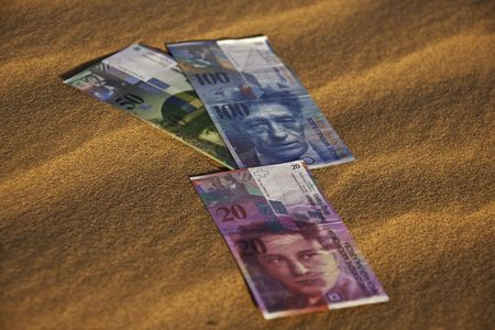 swiss franc note: Swiss currency bank notes laying on sand