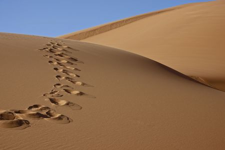 footprints on desert sand dune with blue sky photo