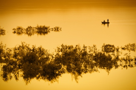 A fishing boat with two men on a lake in orange light.  With copy space.  photo