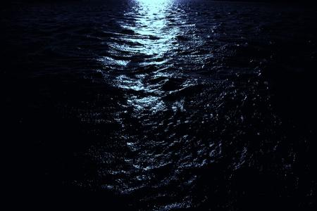the moonlight: Luz de la Luna brilla en agua de mar oscuro. Escena de noche en el mar.   Foto de archivo