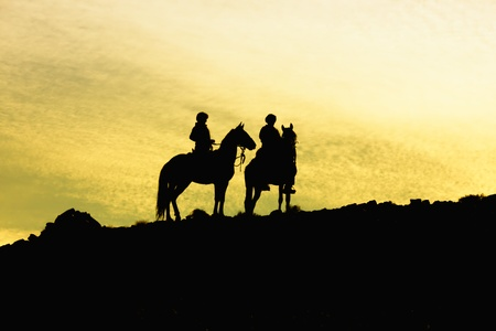 horseback: Silhouette of two horses with riders on a hill, against a yellow sky. Copy space.  Stock Photo