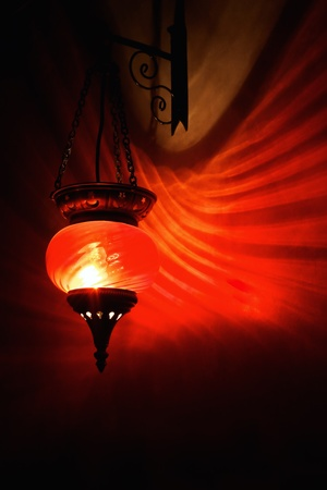 dark interior: Red arabian lamp with shadows on dark wall.  Stock Photo