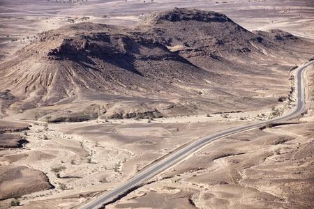 Stony desert landscapes with road and acacia trees, Mhamid, Sahara desert, Morocco.