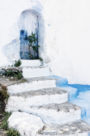 Stone staircase with old, wooden, blue door in Chefchaouen, Morocco.