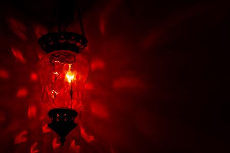 Lampe marocaine rouge foncée contre mur noir. Banque d'images - 85180315