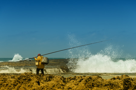 Fisherman at the sea against blue sky.