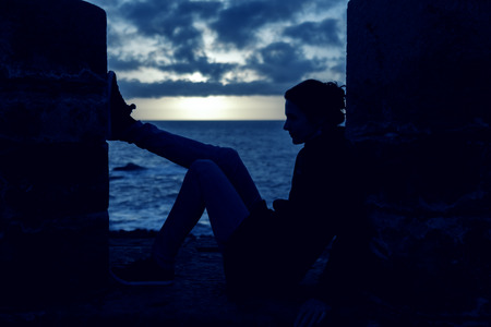 Silhouette of a young woman contemplating sitting on a wall overlooking the sea at sunset. Banco de Imagens
