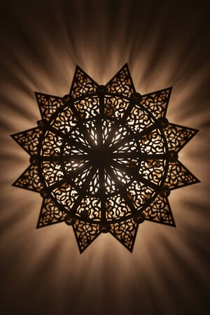 Lit, Moroccan, Arabian lamp with intricate decor. Bottom view. Concept for Moroccan and Arabian culture and design.