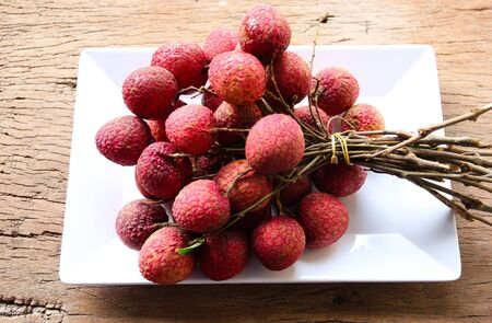 A bunch of fresh lychee in the tray, white on the wooden floor. Stock Photo