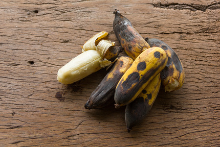 Rotten bananas placed on natural wood plates.