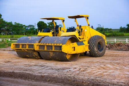 Yellow Steamroller parked on the construction site.During a break. Stock Photo