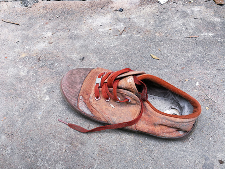 The old defective shoes left on the cement floor. Stock Photo