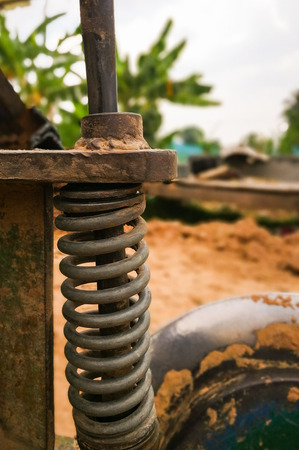 Coil spring of tractor on natural background blur.