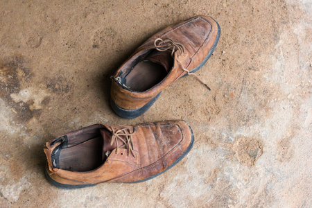 Old and worn brown leather shoes on the cement floor. Standard-Bild - 106148491