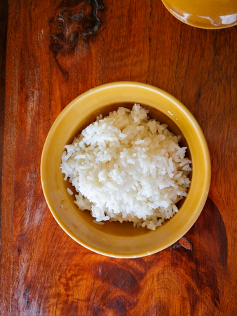 Thai jasmine rice in a brown bowl placed on the dining table made of wood.