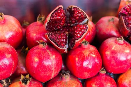 Pomegranate fruit lay stacked and peeled pomegranate on top. Фото со стока