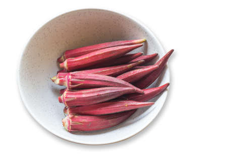 Top view red Okra, Lady's finger, Gombo, Gumbo, Bendee, Quimbamto (Scientific name: Abelmoschus esculentus)stack in a dish, isolated on a white background.