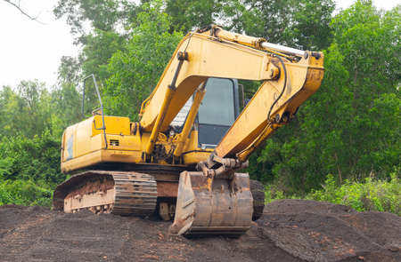 Yellow excavator parked on a pile of crushed stone on natural forest background. Stock Photo