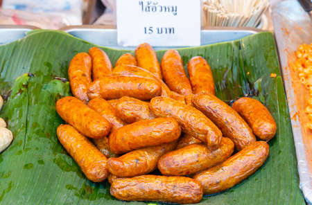 Sai Oua (Sausage), a traditional northern Thai food, placed on fresh banana leaves, sold in local markets with price labels.