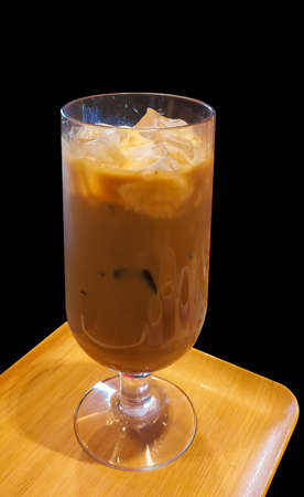 Iced coffee in a clear glass placed on a wooden tray, isolated on a black background. Stock Photo