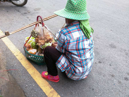 A women hawker wearing a green hat sitting on the roadside selling things The items sold are put in a woven container with a handle on the top to put in the beam.