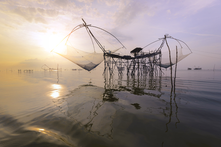 The big fish net trap at dawn under sunrise sky at Pak Pra canal, Phatthalung, Thailand and Sunrise background.