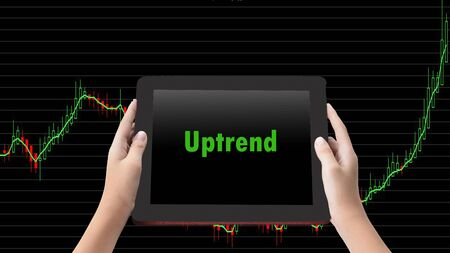 Financial Concept.  Uptrend words in green color on tabled in hands and technical bar chart  background. Zdjęcie Seryjne