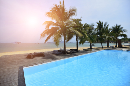 Beautiful Silhouette coconut palm tree on the beach and swimming pool at Luxury Resort . Stock Photo