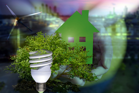Double exposure of Protection  environment  by energy saving concept . Eco home in hand , light bulb , tree and The wind power generation . Stock Photo