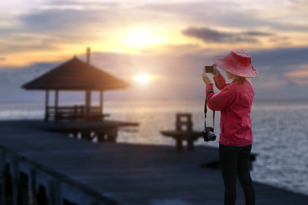 Beautiful women travelers use mobile nature photography and blurred wood bridge as sunrise . Travel concept.