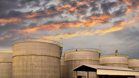 Big industrial oil tanks in a refinery base and beautiful sunset .