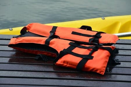 Orange color life jackets,  on Wooden floor . Stock Photo