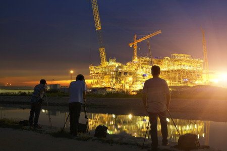 Landscape photographers shooting images photography at construction oil and gas rig plant at twilight. Stock Photo