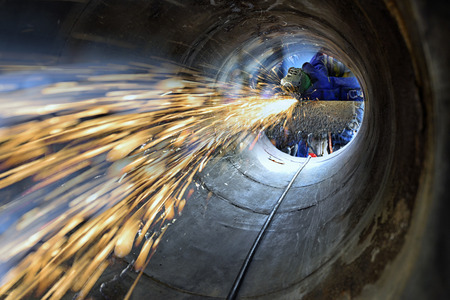 Worker during use electric wheel grinding on steel structure in factory and many sharp sparks inside confined space .