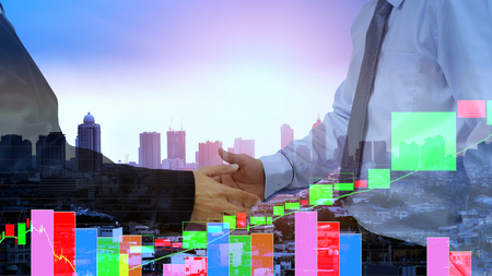 Businessman hand shake for business , stock  chart and city background . Stock Photo