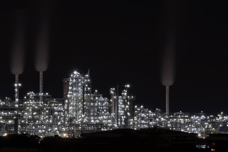 Oil refinery plant at night .