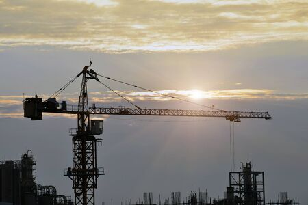 Silhouette tower cranes build large residential buildings  at construction site .