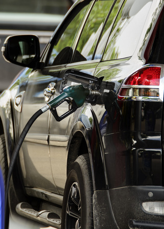 Fill the gas tank ,Gas pump nozzle in the fuel tank of a bronze car, refuel Editorial