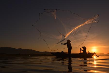 Fisherman on wooden boat on beach sunset Thailand. Stock Photo