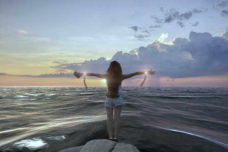 Beautiful girl  has a chain on her wrist  standing on the beach at sunset, freedom concept