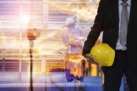 安全建設コンセプト、安全エンジニア持株黄色ヘルメット、ローダーはバックホウ トラック バック グラウンドです。 写真素材
